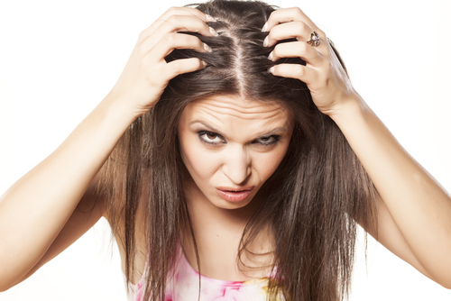 Nervous girl pulling her hair down and looking at her scalp on a white background