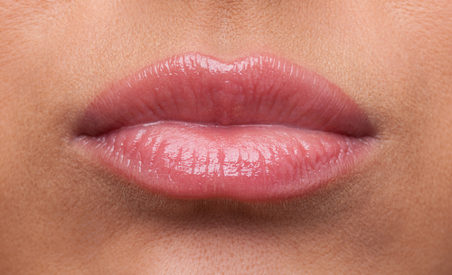 Puckered female lips with pink lipstick