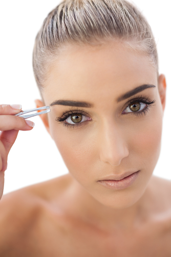 Beautiful woman holding a pair of tweezers next to her eyebrow