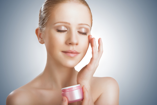 A girl applying skin care cream to her face