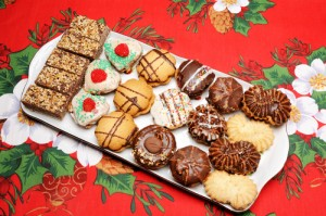 A tray of cookies and brownies on a Christmas floral tablecloth